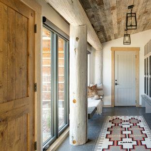 Idéer för mellanstora rustika kapprum, med vita väggar, en enkeldörr och grått golv
