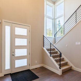 Entryway - mid-sized modern dark wood floor entryway idea in Seattle with beige walls and a white front door