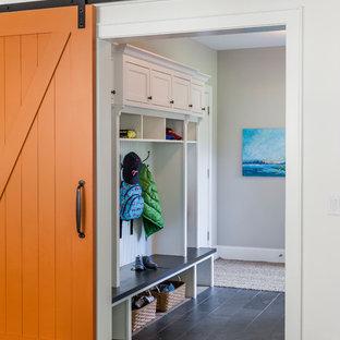 Foto på ett vintage kapprum, med en orange dörr och vita väggar