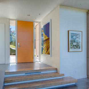 Aménagement d'une porte d'entrée moderne de taille moyenne avec un mur blanc, béton au sol, une porte simple, une porte orange et un sol marron.