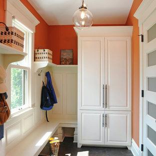 Идея дизайна: тамбур среднего размера в классическом стиле с оранжевыми стенами, полом из сланца и белой входной дверью
