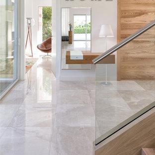Diseño de distribuidor costero, grande, con paredes grises, suelo de mármol, puerta doble, puerta de madera clara y suelo beige