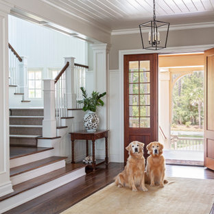 チャールストンの片開きドアビーチスタイルのおしゃれな玄関ロビー (グレーの壁、濃色無垢フローリング、木目調のドア、茶色い床、塗装板張りの天井、羽目板の壁) の写真