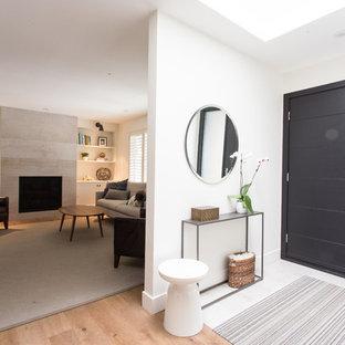 Exempel på en liten 60 tals foajé, med vita väggar, ljust trägolv, en enkeldörr och en svart dörr