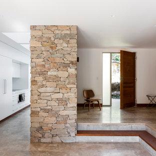 シドニーの片開きドアミッドセンチュリースタイルのおしゃれな玄関ロビー (白い壁、トラバーチンの床、木目調のドア、茶色い床) の写真