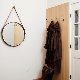 Esempio di un ingresso design con pareti bianche, una porta singola, una porta bianca e pavimento grigio