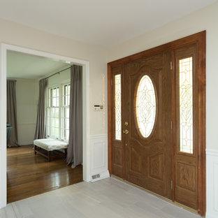 На фото: входная дверь среднего размера в современном стиле с разноцветными стенами, гранитным полом, одностворчатой входной дверью, входной дверью из дерева среднего тона и белым полом с