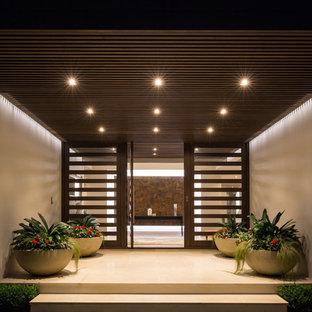 Cette photo montre une grande porte d'entrée tendance avec un mur beige, une porte simple, une porte en bois foncé et un sol beige.