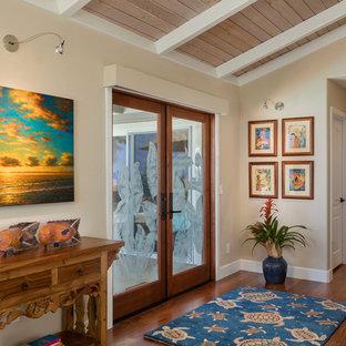 Entryway - mid-sized tropical dark wood floor and brown floor entryway idea in Hawaii with beige walls and a glass front door