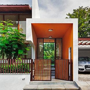 Réalisation d'une porte d'entrée design avec un mur orange, béton au sol, un sol gris et une porte simple.