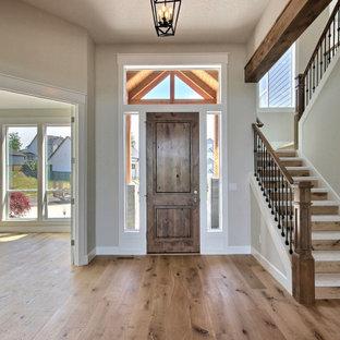 Inredning av en klassisk mycket stor foajé, med beige väggar, ljust trägolv, en enkeldörr, mellanmörk trädörr och brunt golv