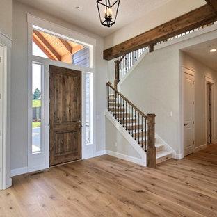 ポートランドの巨大な片開きドアトランジショナルスタイルのおしゃれな玄関ロビー (ベージュの壁、淡色無垢フローリング、木目調のドア、茶色い床、表し梁) の写真