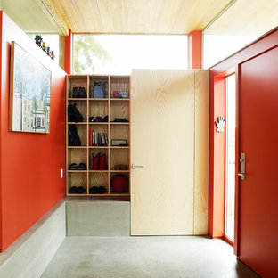 Example of an urban concrete floor entryway design in Seattle with red walls and a red front door