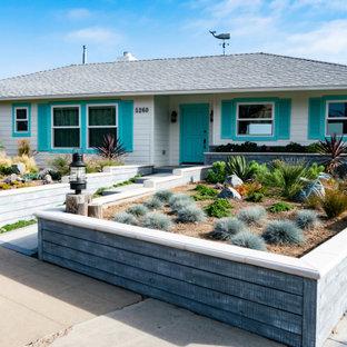 サンディエゴの中くらいのダッチドアビーチスタイルのおしゃれな玄関ドア (白い壁、セラミックタイルの床、青いドア、グレーの床、塗装板張りの天井、パネル壁) の写真