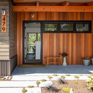 Immagine di una porta d'ingresso minimalista di medie dimensioni con pareti multicolore, pavimento in legno massello medio, una porta singola, una porta nera, pavimento marrone e travi a vista