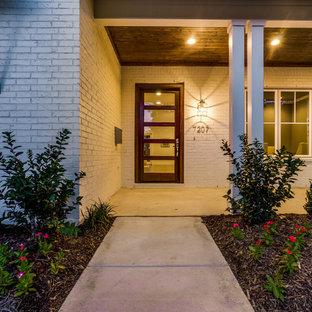 Réalisation d'une porte d'entrée tradition de taille moyenne avec un mur blanc, béton au sol, une porte simple et une porte en verre.