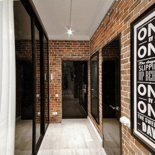 Ejemplo de hall urbano con paredes rojas, suelo de madera clara, puerta simple y puerta negra