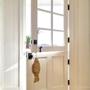 サンフランシスコのダッチドアビーチスタイルのおしゃれな玄関 (白い壁、無垢フローリング、白いドア、茶色い床、表し梁、塗装板張りの天井、三角天井、塗装板張りの壁) の写真