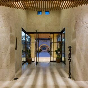 オースティンの大きい回転式ドアコンテンポラリースタイルのおしゃれな玄関ロビー (ベージュの壁、トラバーチンの床、金属製ドア) の写真