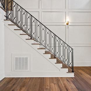 На фото: большое фойе в классическом стиле с белыми стенами, паркетным полом среднего тона, двустворчатой входной дверью, входной дверью из темного дерева, коричневым полом, сводчатым потолком и панелями на стенах