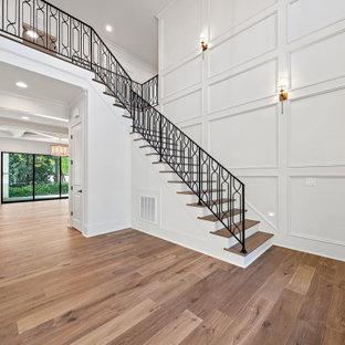 Großer Klassischer Eingang mit Foyer, weißer Wandfarbe, braunem Holzboden, Doppeltür, dunkler Holztür, braunem Boden, gewölbter Decke und vertäfelten Wänden in Raleigh
