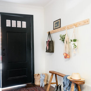Small transitional medium tone wood floor and brown floor entryway photo in Dallas with white walls and a black front door