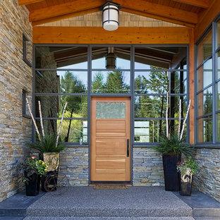 Imagen de puerta principal contemporánea con puerta simple, paredes marrones, moqueta, puerta de madera en tonos medios y suelo gris