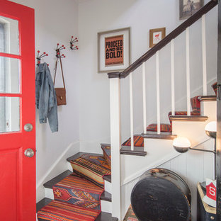 Inspiration for a small eclectic concrete floor entryway remodel in Chicago with white walls and a red front door