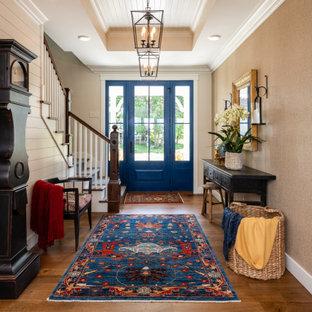 Exemple d'un hall d'entrée nature avec un mur beige, un sol en bois brun, une porte simple, une porte bleue, un sol marron, un plafond en lambris de bois, du lambris de bois et du papier peint.
