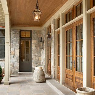 Foto de entrada clásica, extra grande, con puerta simple y puerta de madera en tonos medios