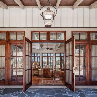他の地域の両開きドアトラディショナルスタイルのおしゃれな玄関 (ピンクの壁、ライムストーンの床、木目調のドア) の写真