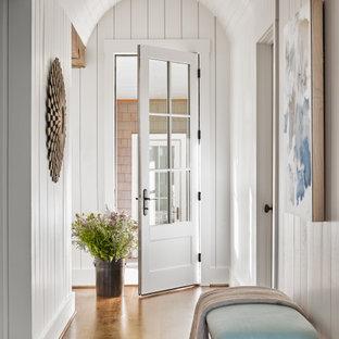 Inspiration för klassiska hallar, med vita väggar, mellanmörkt trägolv, en enkeldörr, en vit dörr och brunt golv