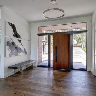 Cette photo montre une grande porte d'entrée tendance avec un mur orange, un sol en bois brun, une porte simple, une porte en bois brun et un sol marron.