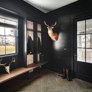Country brown floor entryway photo in Nashville with black walls and a black front door