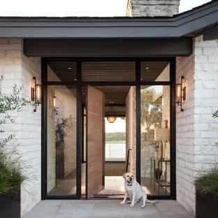 Источник вдохновения для домашнего уюта: входная дверь в современном стиле с белыми стенами, поворотной входной дверью, входной дверью из дерева среднего тона и серым полом