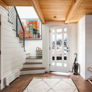 シアトルの片開きドアビーチスタイルのおしゃれな玄関ロビー (白い壁、濃色無垢フローリング、白いドア、茶色い床、表し梁、板張り天井、塗装板張りの壁) の写真