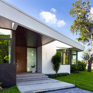 Inspiration for a contemporary front door in Miami with white walls, a single front door, a medium wood front door and grey floors.