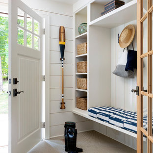 Example of a beach style carpeted and beige floor entryway design in Minneapolis with white walls and a white front door