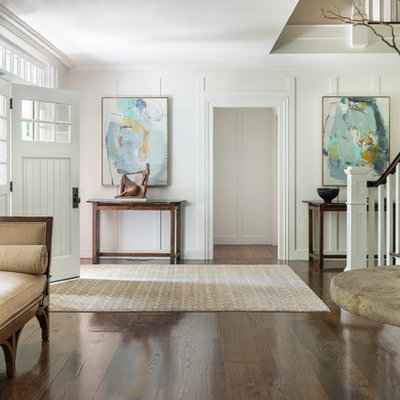 Example of a transitional dark wood floor entryway design in New York with white walls and a white front door