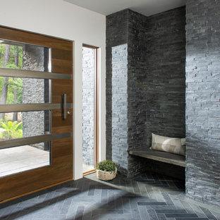 Idee per un ingresso minimal con pareti bianche, una porta a pivot, una porta in legno scuro e pavimento grigio