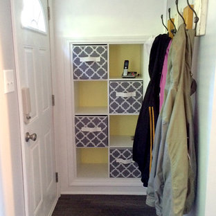 Example of a small trendy medium tone wood floor entryway design in Other with gray walls and a white front door