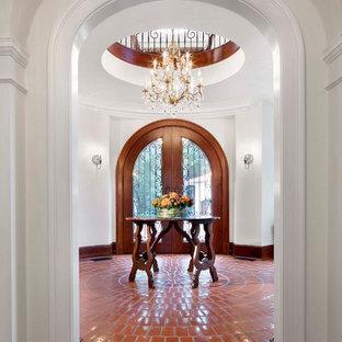シカゴの両開きドア地中海スタイルのおしゃれな玄関ロビー (白い壁、テラコッタタイルの床、ガラスドア、赤い床) の写真
