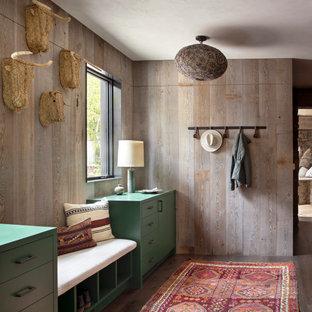 Idée de décoration pour une entrée chalet avec un vestiaire, un mur marron, un sol en bois brun et un sol marron.