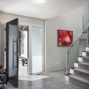 Ispirazione per un ingresso minimalista di medie dimensioni con pareti grigie, pavimento alla veneziana, una porta singola, una porta in legno scuro e pavimento grigio