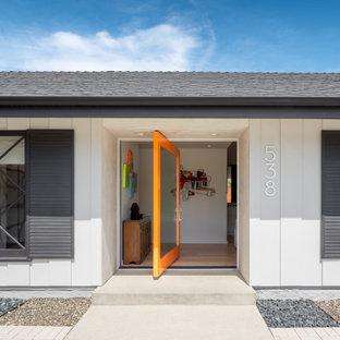 Inspiration för en funkis ingång och ytterdörr, med vita väggar, ljust trägolv, en pivotdörr, en orange dörr och beiget golv
