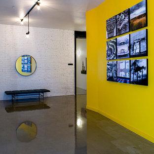 Esempio di una grande porta d'ingresso industriale con pareti gialle e pavimento in cemento