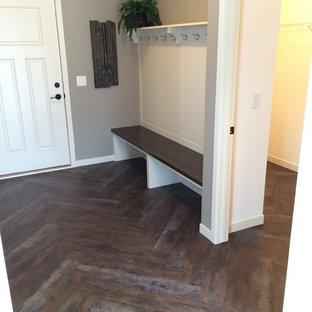 Klassisk inredning av ett mellanstort kapprum, med grå väggar, mörkt trägolv, en enkeldörr och en vit dörr