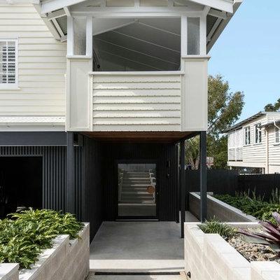 Example of a trendy beige floor entryway design in Brisbane with a glass front door