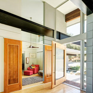 Large trendy light wood floor entryway photo in Other with a medium wood front door and beige walls