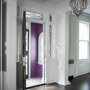 Ejemplo de distribuidor clásico, grande, con puerta doble, puerta negra, paredes púrpuras y suelo de madera oscura